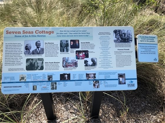 Sign at Newton Beach Park with information about the history of Seven Seas Cottage