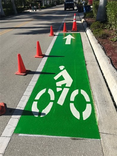 Green marking on Estero Boulevard for bike lane with arrow and stick person on a bike